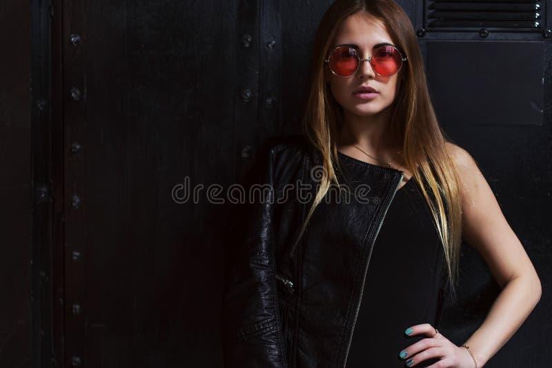 Manierfoto van aantrekkelijk vrouwelijk model in de agressieve kleren van de rotsstijl en roze zonnebril die in donker binnenland stock foto