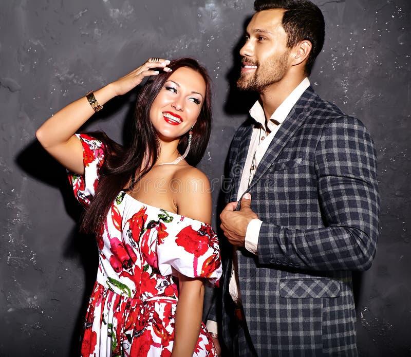 Manierfoto van de knappe elegante mens in kostuum met het mooie sexy vrouw stellen dichtbij grijze muur royalty-vrije stock foto's