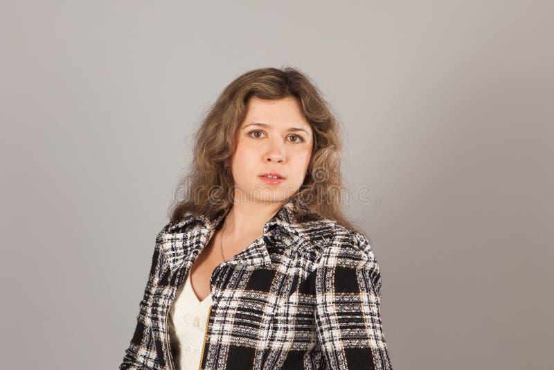 Manierfoto van een jonge vrouw met krullend haar die wit kleding en jasje dragen stock afbeelding