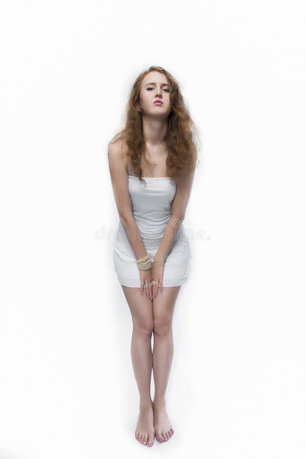 Manierfoto van een jonge vrouw met krullend haar die witte kleding dragen royalty-vrije stock afbeelding