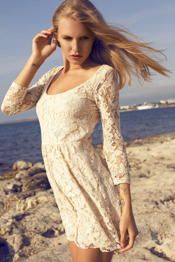 Manierfoto van het mooie blonde meisje stellen op strand stock foto's