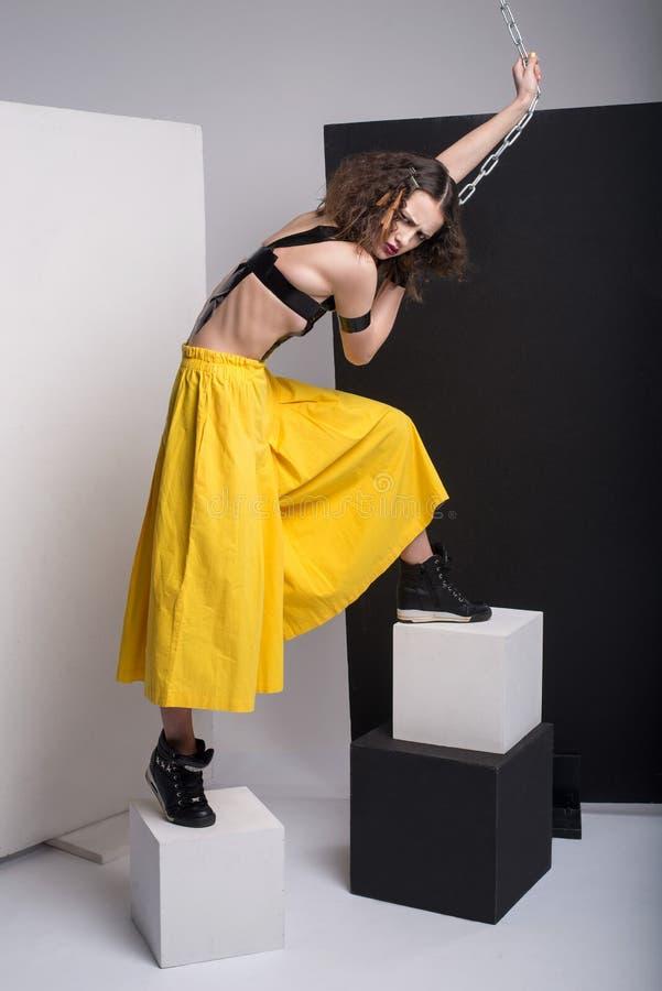 Manierfoto van het mooie meisje stellen in studio Het dragen van gele borrels, zwarte laarzen Riemen over de keten van de borstho stock fotografie