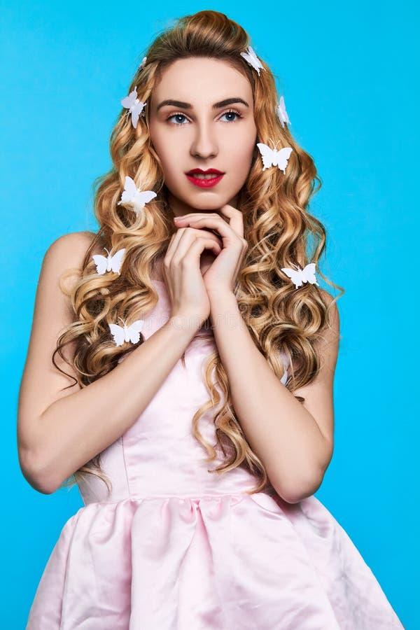 Manierfoto van jonge vrouw tegen blauwe achtergrond die roze kleding dragen en haar de spelden kijken als vlinders stock afbeeldingen
