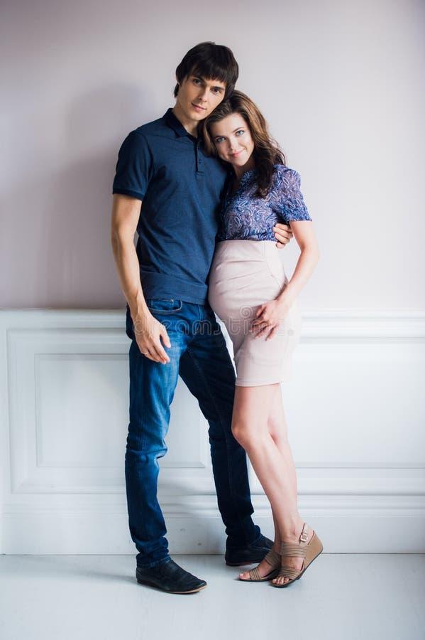 Manierfoto van mooi paar in elegante kleren het knappe jonge mens stellen met schitterende zwangere vrouw stock afbeelding