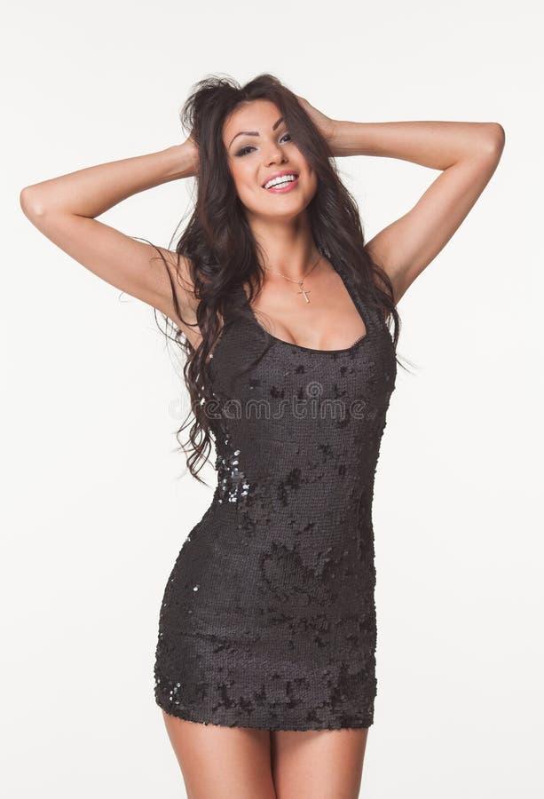 Manierfoto van mooie donkerbruine vrouw in de zwarte zomer jumpsuit liften, glas en metaal Het concept van de verkoop en van kort stock afbeeldingen