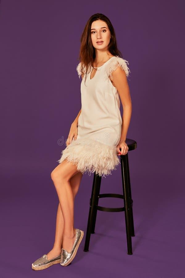 Manierfoto van mooie vrouw met donkerbruin haar in het witte kleding stellen op stoel bij studio royalty-vrije stock afbeelding