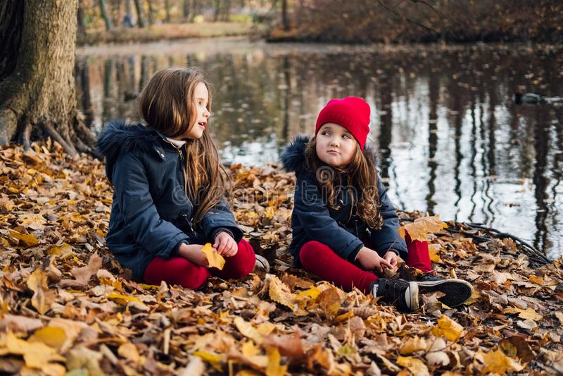 Manierjonge geitjes in de herfstpark Sluit omhoog levensstijlportret van twee mooie Kaukasische meisjes die in openlucht, leuke i stock afbeelding