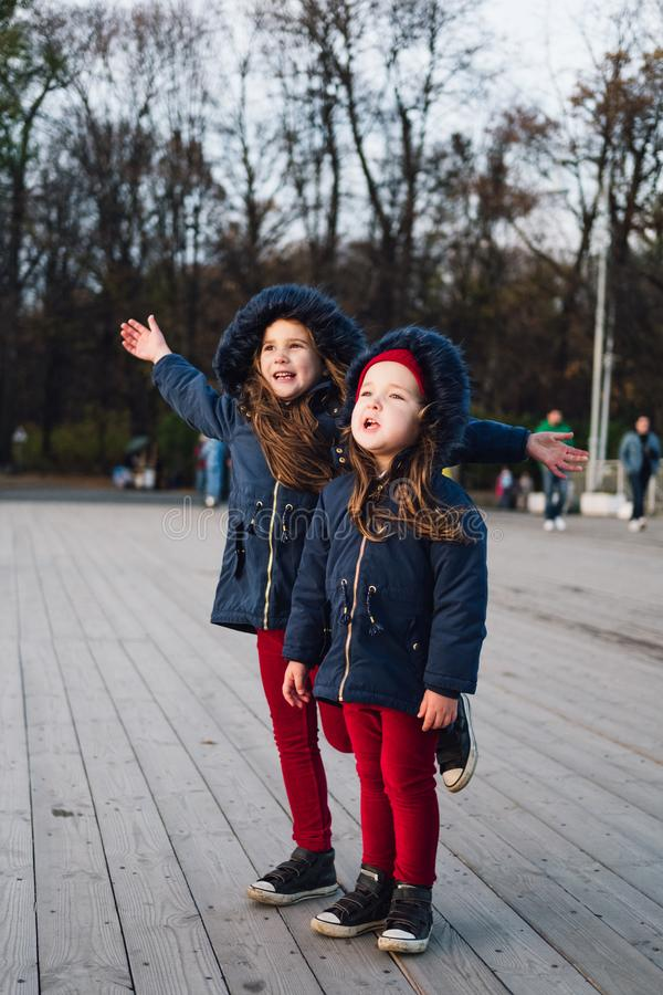 Manierjonge geitjes in de herfstpark Sluit omhoog levensstijlportret van twee mooie Kaukasische meisjes die in openlucht, leuke i royalty-vrije stock afbeelding