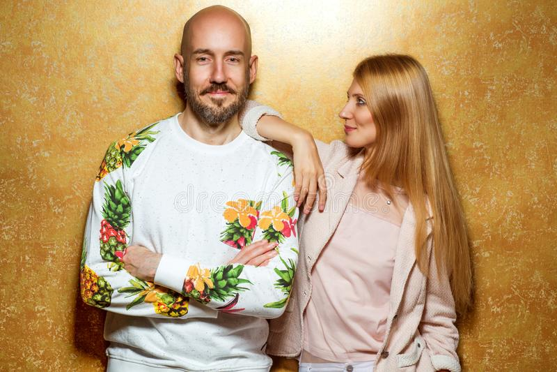 Manierkerel met een meisje in studio het stellen op gouden backgroun royalty-vrije stock foto
