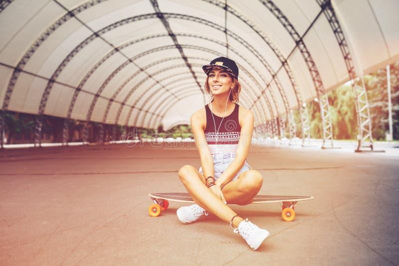Manierlevensstijl, mooie jonge vrouw met longboard royalty-vrije stock fotografie