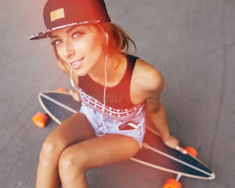 Manierlevensstijl, mooie jonge vrouw met longboard stock foto