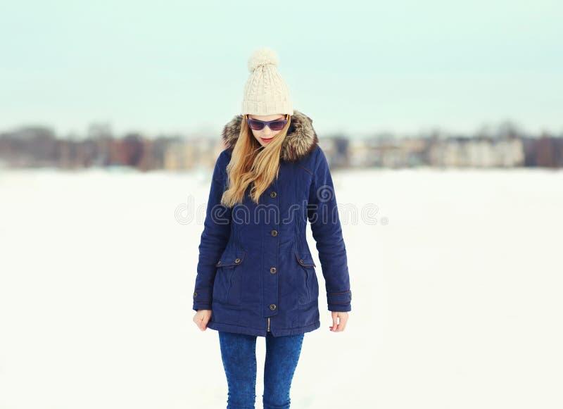 Maniermeisje die een jasje, een hoed en zonnebril in de winter dragen stock foto