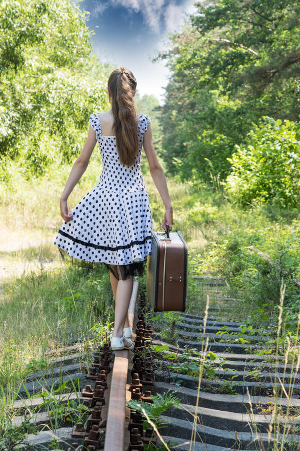 Maniermeisje met koffer bij spoorwegen royalty-vrije stock afbeelding