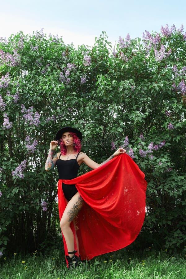 Maniermeisje met rood haar en grote ronde hoed, de lenteportret in lilac kleuren in de zomer Mooie rode roze kleding, tatoegering stock foto