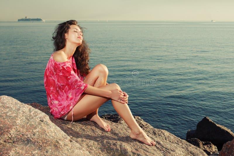 Maniermeisje op het strand op rotsen tegen de achtergrond van royalty-vrije stock afbeeldingen