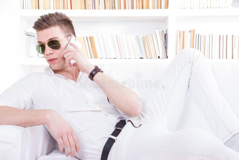 Maniermens die zonnebril dragen die op telefoon ontspannen indo spreken stock afbeeldingen