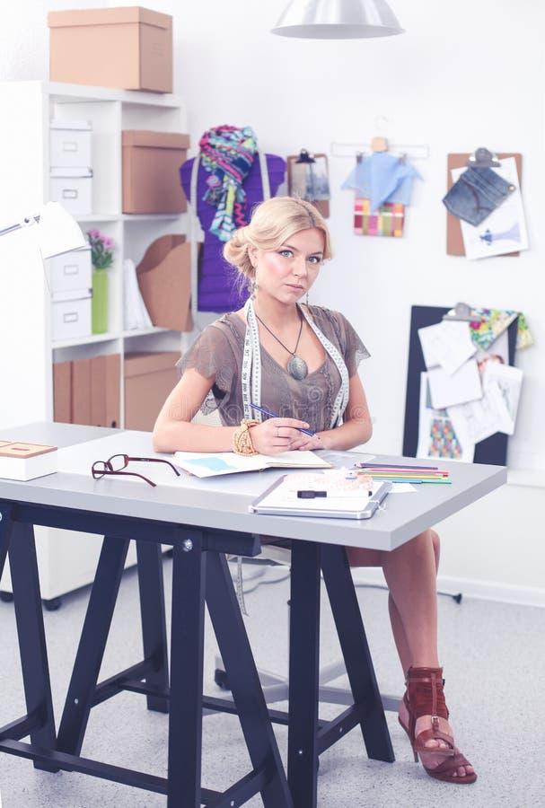 Manierontwerper die aan haar ontwerpen in de studio werken stock fotografie