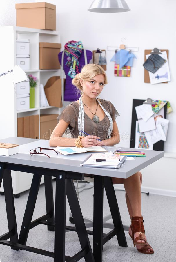 Manierontwerper die aan haar ontwerpen in de studio werken stock afbeeldingen