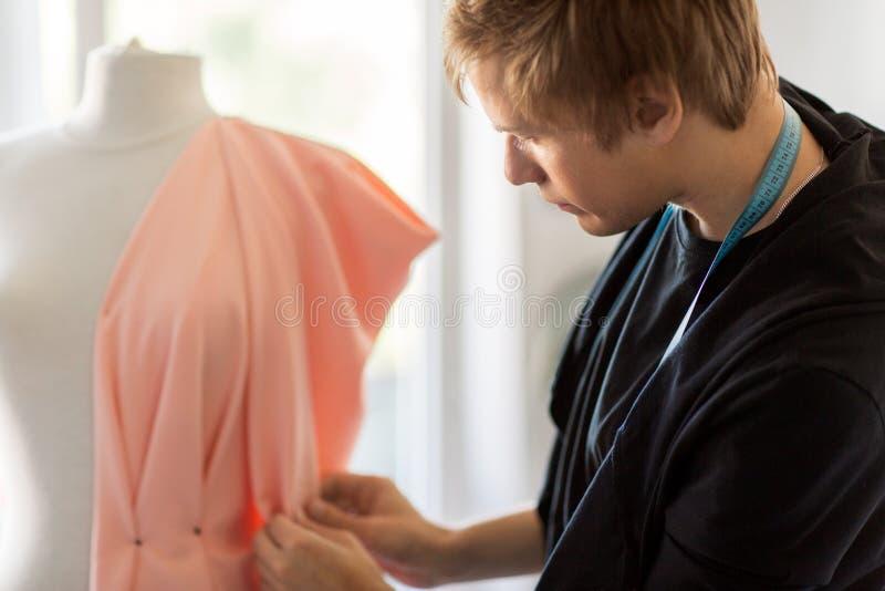 Manierontwerper die met model kleding maken bij studio stock afbeelding