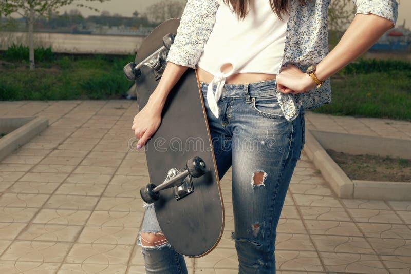 Manierportret die van wijfje een skateboard houden stock afbeelding