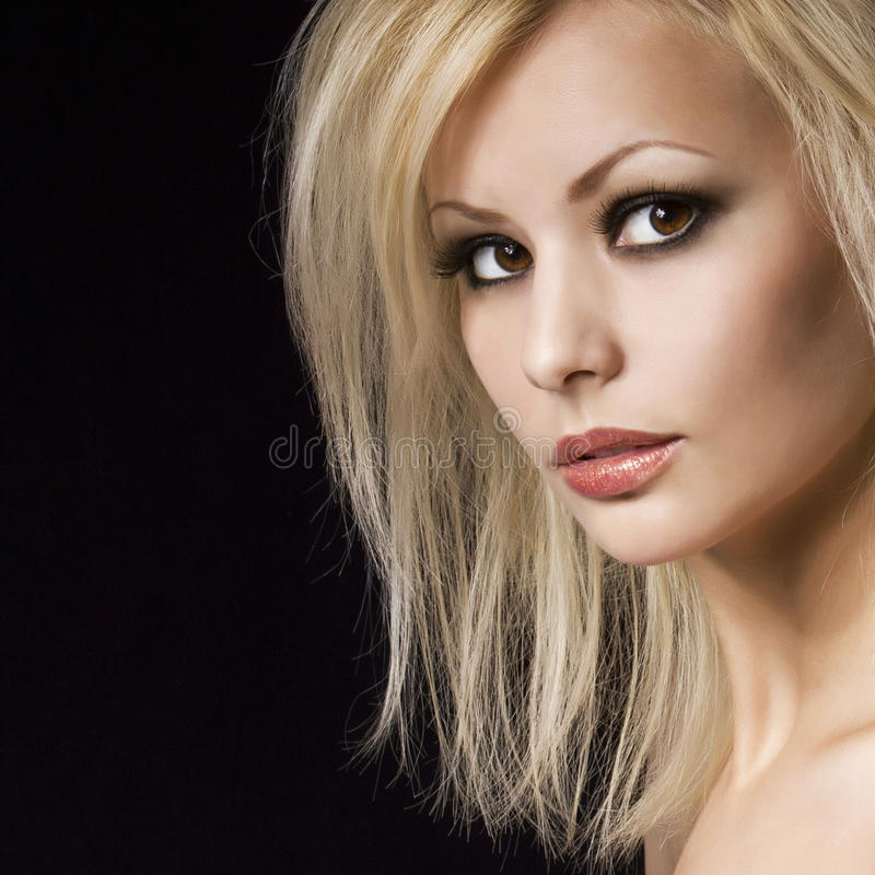 Manierportret. Mooie blondevrouw met professioneel make-up en kapsel, over zwarte. Vogue-stijlmodel royalty-vrije stock afbeeldingen