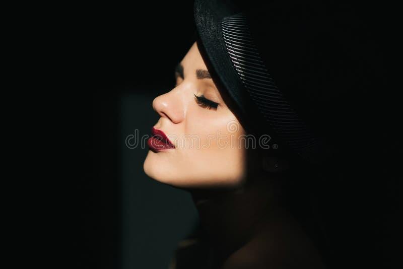 Manierportret in profiel van een jong sexy meisje in een zwarte hoed met rode lippenstift stock foto's