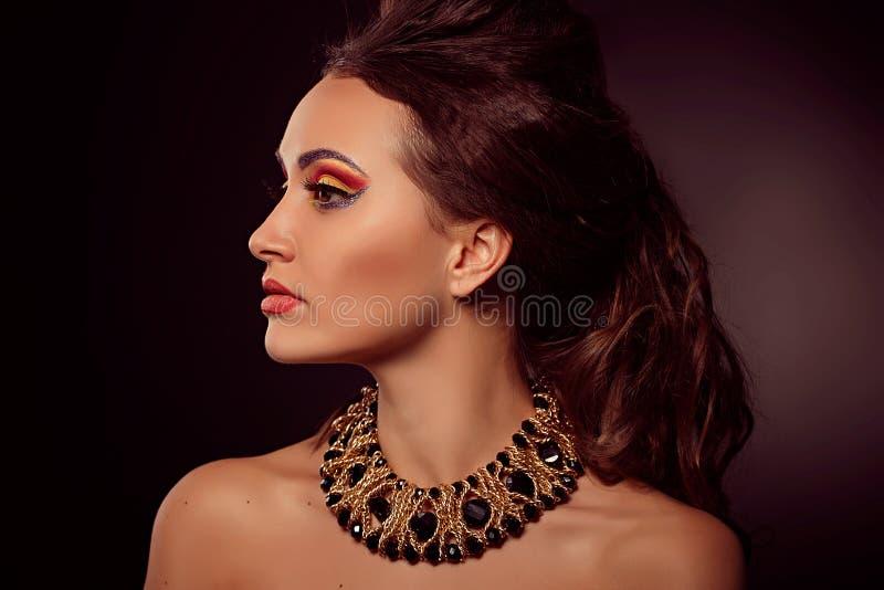 Manierportret van bruin-ogenvrouw Gouden Juwelen Oranje yello royalty-vrije stock afbeeldingen