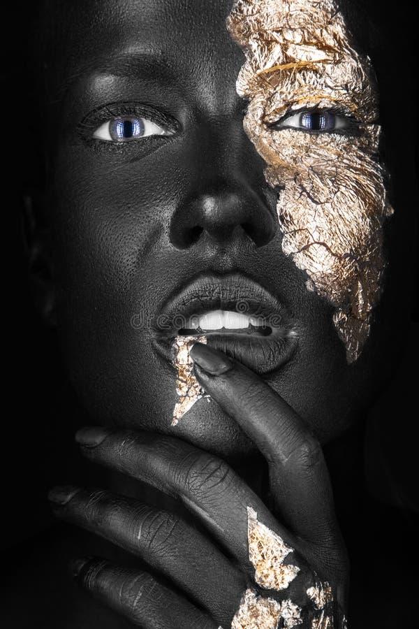 Manierportret van een donker-gevild meisje met goud royalty-vrije stock afbeeldingen