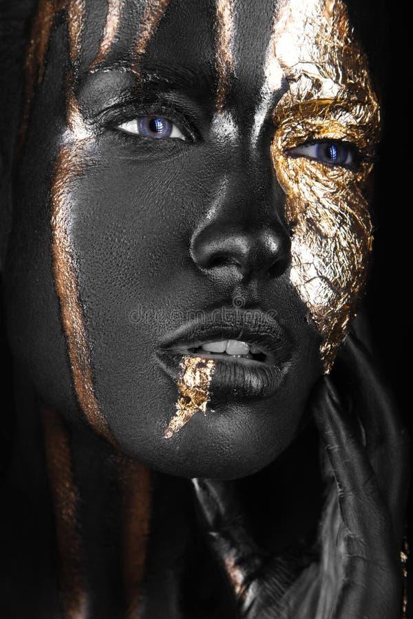 Manierportret van een donker-gevild meisje met gouden samenstelling Het Gezicht van de schoonheid royalty-vrije stock fotografie
