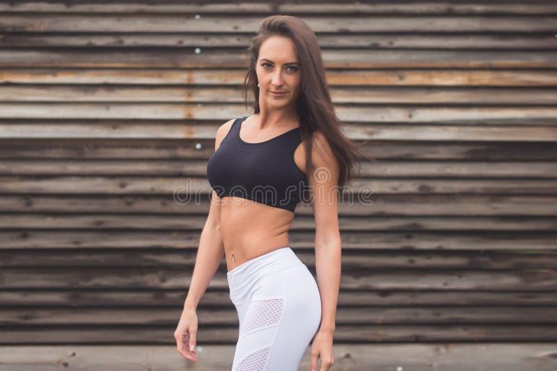 Manierportret van een jong atletisch geschikt meisje in sportkleding in openlucht Vrouw met het perfecte concept van de lichaamsg royalty-vrije stock foto