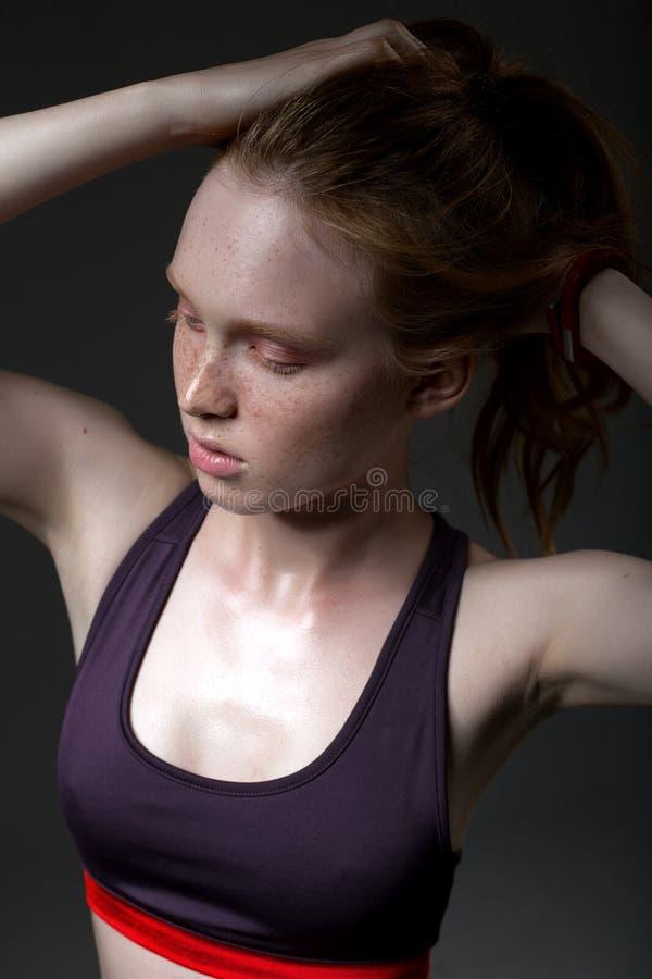 Manierportret van een jong meisje in een sportenbovenkant op een donkere achtergrond stock fotografie
