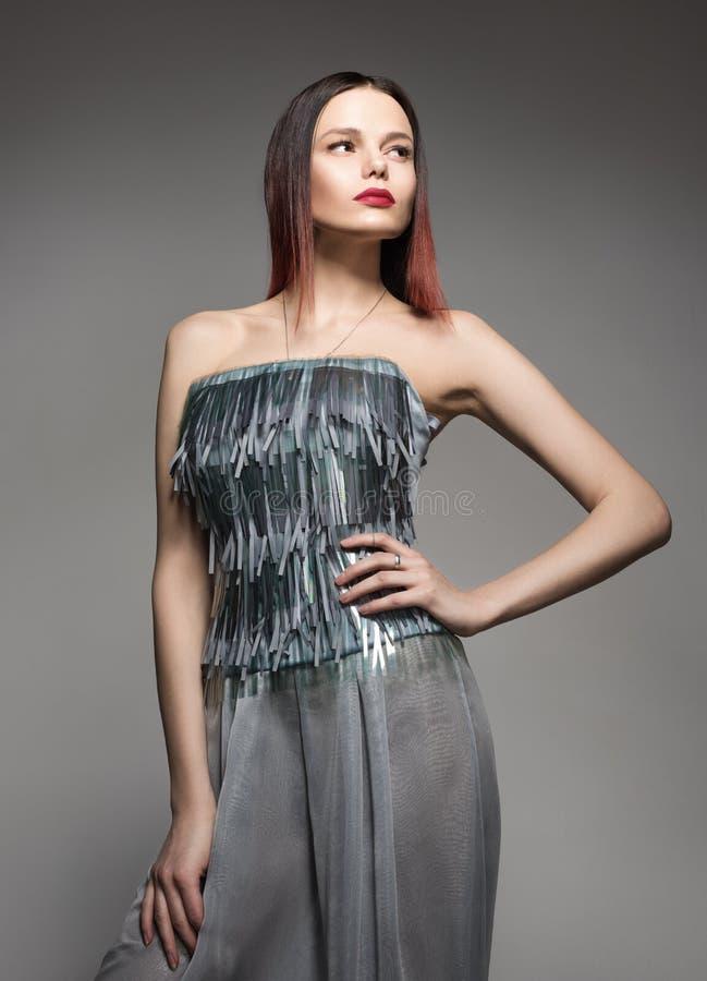 Manierportret van een jonge vrouw in een mooie grijze kleding Professionele Samenstelling stock foto