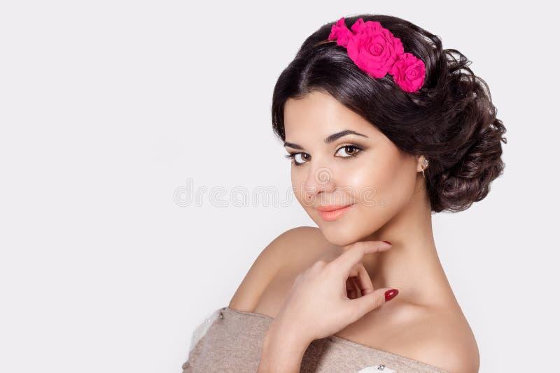 Manierportret van een mooi sexy leuk brunette met mooi modieus kapsel, heldere make-up en bloemen in haar haar stock fotografie