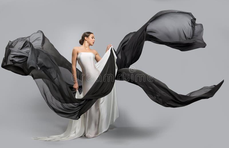 Manierportret van een mooie vrouw in een witte en zwarte kleding De stoffenvliegen in de wind stock afbeelding