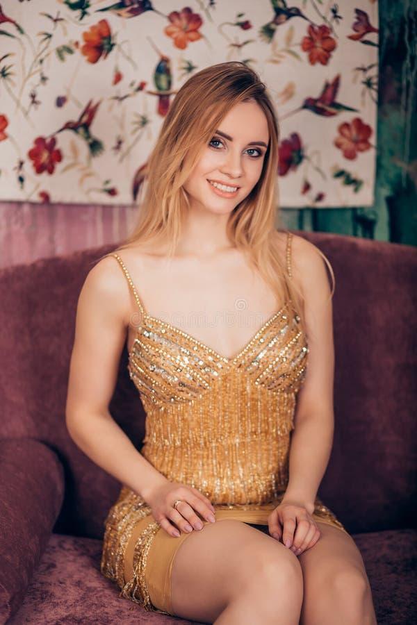 Manierportret van een schitterende blondevrouw die een korte glanzende Gouden kleding dragen en de camera in de Studio bekijken G stock afbeelding