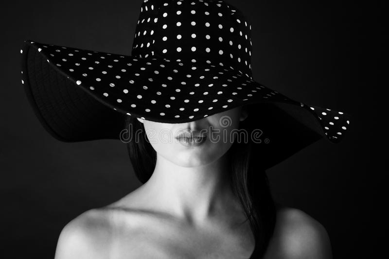 Manierportret van een vrouw met zwart-witte van de puntenhoed en steenbolk lippen stock afbeelding