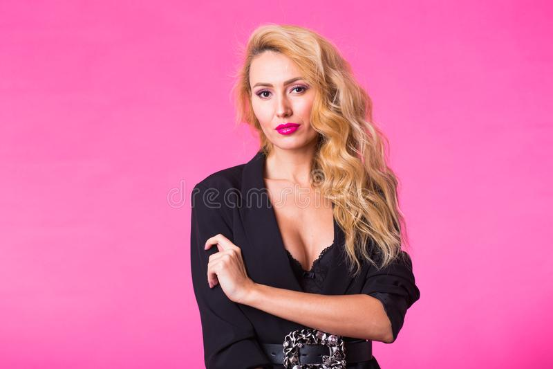 Manierportret van elegante jonge vrouw met krullend blondehaar over roze achtergrond royalty-vrije stock afbeelding