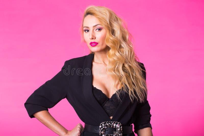 Manierportret van elegante jonge vrouw met krullend blondehaar over roze achtergrond stock foto's