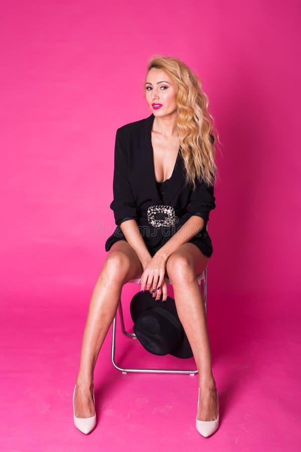 Manierportret van elegante jonge vrouw met krullend blondehaar over roze achtergrond stock afbeeldingen
