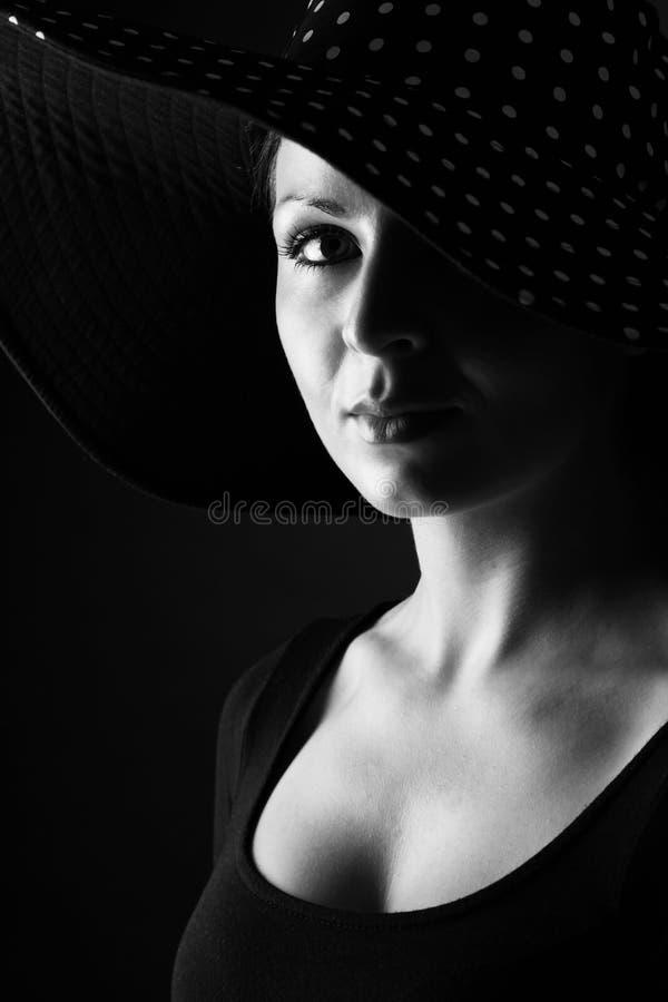 Manierportret van elegante vrouw in zwart-witte hoed stock foto's