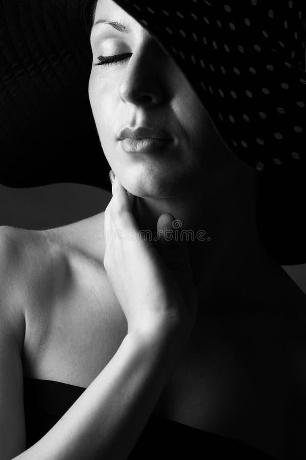 Manierportret van elegante vrouw in zwart-witte hoed stock fotografie