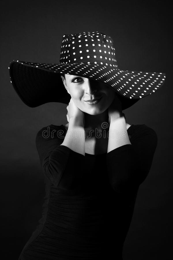 Manierportret van elegante vrouw in zwart-witte hoed stock afbeelding