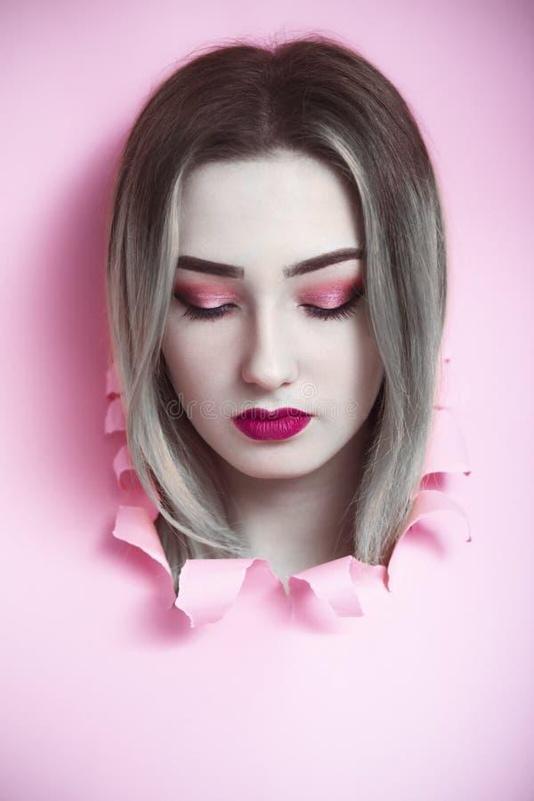 Manierportret van jong vrouwenhoofd in een gat van roze kartondocument, het gezicht van een meisje met make-up, het concept schoo stock foto's