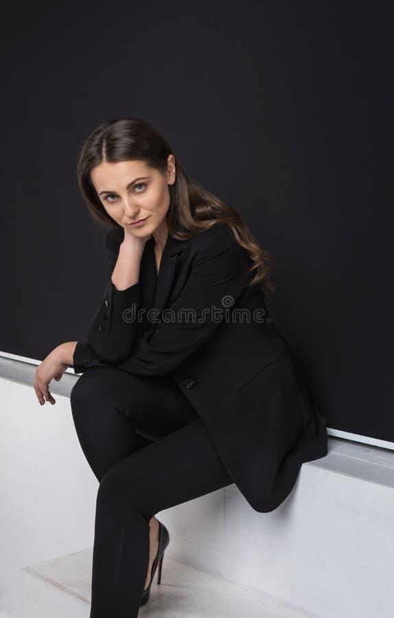 Manierportret van jonge elegante vrouw in zwart kostuum studio royalty-vrije stock afbeeldingen