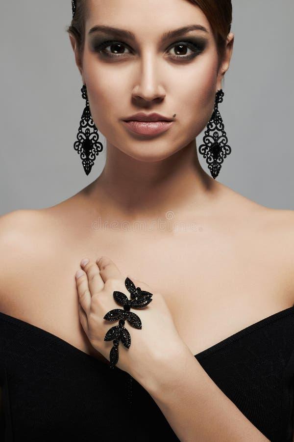 Manierportret van jonge mooie sexy vrouw in juwelen Elegante dame in zwarte kleding stock afbeelding