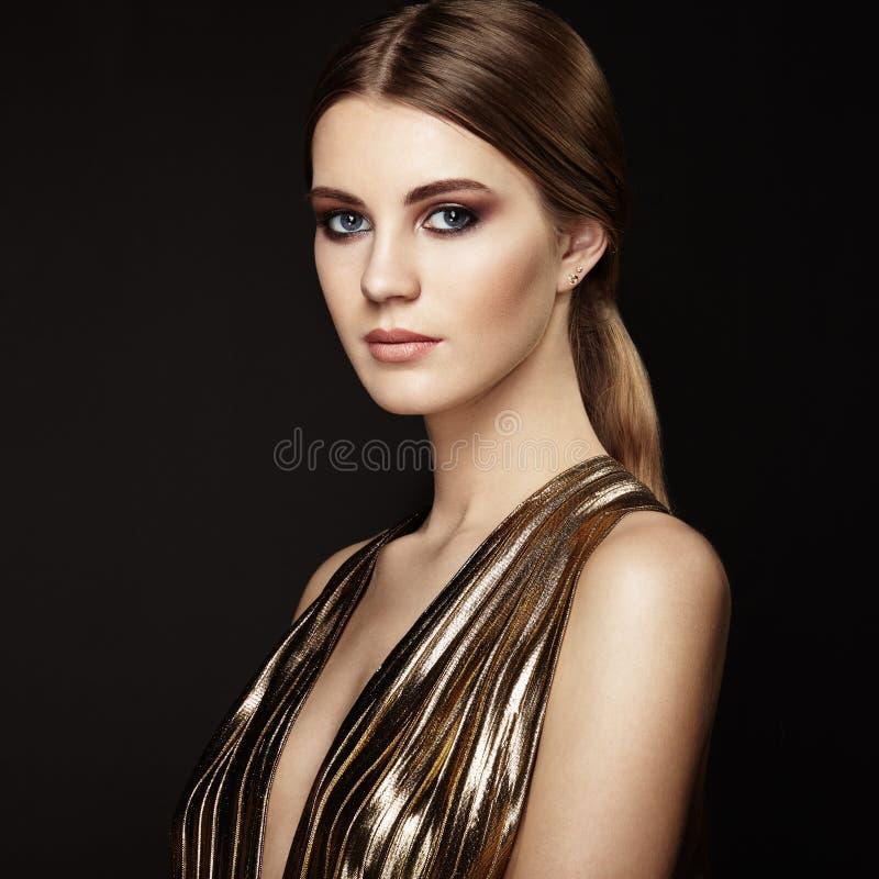 Manierportret van jonge mooie vrouw in gouden kleding royalty-vrije stock afbeelding