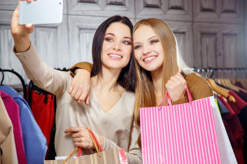 Manierportret van twee jonge mooie vrouwenvrienden in winkelcomplex met heel wat het winkelen zakken Het maken selfie royalty-vrije stock fotografie