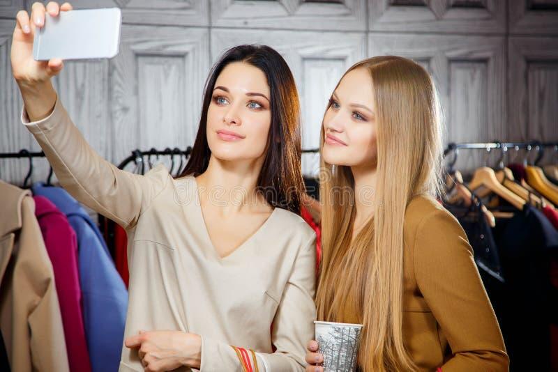 Manierportret van twee jonge mooie vrouwenvrienden in winkelcomplex met heel wat het winkelen zakken Het maken selfie stock afbeeldingen
