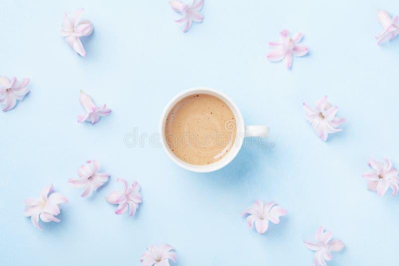 Maniersamenstelling met ochtendkop koffie en roze bloemen op blauwe pastelkleur hoogste mening als achtergrond vlak leg stijl royalty-vrije stock fotografie