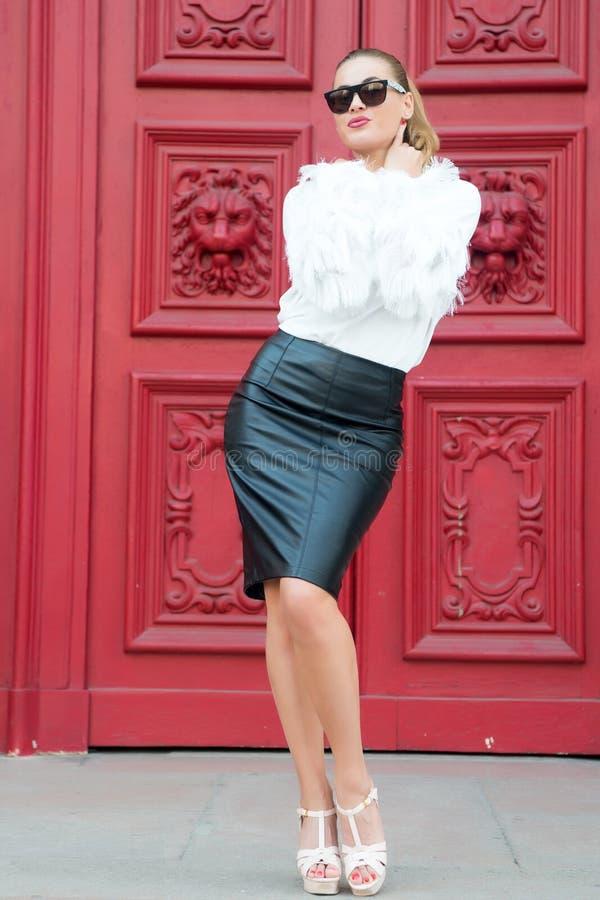 Manierschoonheid en mode Vrouw in hoge hielschoenen op rode deur in Parijs, Frankrijk Sexy vrouw in zonnebril met lang haar Schoo royalty-vrije stock foto's